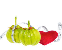 Garcinia cambogia fresh fruit with red heart and measuring tape,. Isolated on white. Garcinia is spice plants. It helps in the metabolism contain high vitamin C Stock Photo