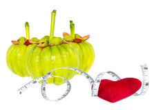 Garcinia cambogia fresh fruit with red heart and measuring tape,. Isolated on white. Garcinia is spice plants. It helps in the metabolism contain high vitamin C Royalty Free Stock Photo