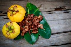 Garcinia cambogia fresh fruit on wood background.  Fruit for die. Top view. Garcinia cambogia fresh fruit on wood background. Dry garcinia on leaf. Garcinia Stock Photos