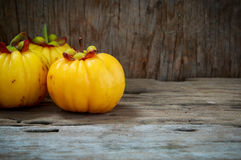 Garcinia cambogia fruit on wood background.  Fruit for diet and Stock Photo