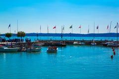 Garda lake, Sirmione, Italy. Port in lake Garda. Different flags stock image