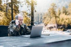 Garde-chasse adulte avec l'ordinateur portable et le smartphone Image stock