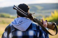 Garde-chasse brutal de type d'homme à l'arrière-plan de nature de chapeau Brutalité et masculinité Le chasseur portent le pistole photo stock