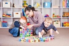 Garde d'enfants jouant le jeu de bloc de gosses avec des enfants Image libre de droits