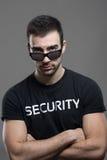 Garde de sécurité masculin dur fâché avec le regard menaçant au-dessus des lunettes de soleil images libres de droits