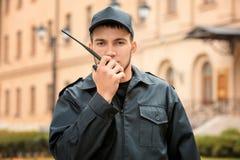 Garde de sécurité masculin utilisant l'émetteur radioélectrique portatif Photographie stock libre de droits