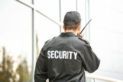 Garde de sécurité masculin utilisant l'émetteur radioélectrique portatif photographie stock