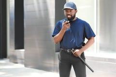 Garde de sécurité masculin utilisant l'émetteur radioélectrique portatif Photo stock