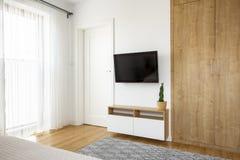 Garde-robe en bois à côté de télévision sur le mur blanc dans le bedroo d'hôtel photographie stock libre de droits