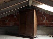 Garde-robe en bois dans le grenier inhabité poussiéreux Images stock