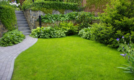 Garden. Stone path with grass growing up between the stones royalty free stock photography