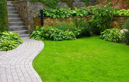 Garden. Stone path with grass growing up between the stones Stock Image