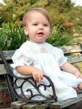 In the Garden. Baby sitting on littled park bench in a flower garden Stock Image