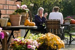 In the garden. Two woman having conversation at the garden table with autumn decoration Stock Photo