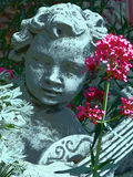 Garden angel. Figure of an angel in a bed of flowers Stock Photos