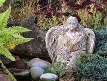 Garden Angel. Appalachian Mountains, North Carolina. Old concrete angel garden on Beech Mountain. Evergreens, Maidenhair Fern, Red Sedum, and rocks Stock Images