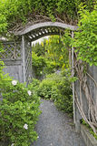 Garden Arbor. Wooden arbor and fence in a perennial garden or park like setiing Stock Photos