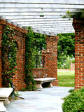 Garden Arbor. Pretty brick and wood arbor in the garden Stock Image