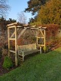 Garden arbor with bench. Garden arbor and wooden bench in a secluded garden setting Royalty Free Stock Images