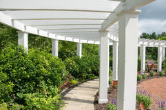 Garden Arbor. An arbor in a garden surrounded by bushes and flowers Royalty Free Stock Photos