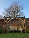 Garden arbor with bench. Garden arbor and wooden bench in a secluded garden setting Stock Image