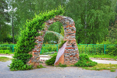 Garden arch in stone the conifers. The territory of the Central Siberian Botanical garden, Novosibirsk, Siberia, Russia - June 25, 2017: garden arch with Royalty Free Stock Photography