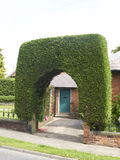 Garden arch UK. Entrance to a garden with arch shaped tree Royalty Free Stock Photo