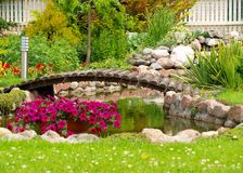 Garden Arched Bridge. Little artificial pond and flowers in the garden Royalty Free Stock Photo
