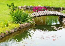 Garden Arched Bridge. Little artificial pond and flowers in the garden Royalty Free Stock Photography