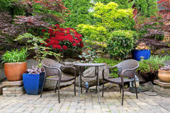 Garden Backyard Landscaping with Bistro Furniture springtime. Garden backyard with lush plants landscaping and stone paver patio hardscape with wicker bistro Royalty Free Stock Image