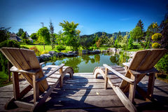 Garden Backyard Pond. With Adirondack Chair Set royalty free stock image