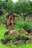 Garden backyard with wooden decorative mill and stones. Garden backyard with wooden decorative mill, flowers and stones; alpine slides Royalty Free Stock Image