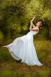 The garden is a beautiful girl soars. She in lightweight white dress Stock Photos