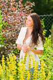 Garden beautiful young woman sunny yellow flowers Royalty Free Stock Image