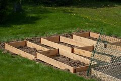 Garden Beds Nearing Completion. Raised beds, made of cedar, were built and are being placed and leveled prior to filling with compost and soil royalty free stock photos