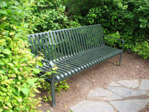 Garden Bench. A deep green metal garden bench sits tucked into the bushes, just off the stone pathway. An aesthetic contribution to any walk and durable enough Royalty Free Stock Image