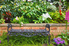 Garden Bench. Pretty garden bench surrounded by flowers and greenery royalty free stock photos