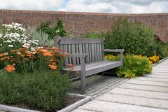 Garden Bench. Wooden oak garden bench inside a walled garden with flowers and shrubs royalty free stock photography