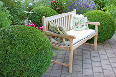 Garden bench between boxwood Royalty Free Stock Photo