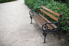 Garden bench. Decorative garden bench on the path in the park stock images