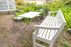 Garden bench. Garden furniture: white bench, table and chairs in a garden in Denmark, 2017 royalty free stock photography
