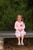 Garden Bench with Girl. A beautiful little girl sitting on a garden bench Stock Photography