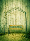 Garden bench. Idyllic image with a garden bench under a metal arbor, near the wooden wall of a barn, in a german residence backyard Royalty Free Stock Photo