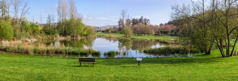 Garden bench overlooking the lake or pond of Parque da Devesa Urban Park in Vila Nova de Famalicao. Portugal. Built near the center of the city. View of the Royalty Free Stock Images