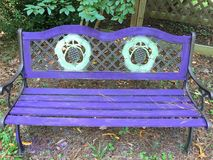 Garden Bench painted purple and yellow. Garden bench sitting in a mulched area with foliage and a lattice fence as a background. Bench is painted wood and has stock photography
