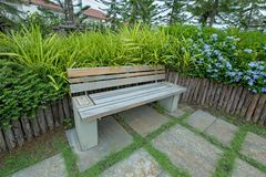 Garden bench surrounded by flower. Old Wooden bench in the park stock photography