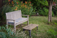 Garden bench and table. A weathered wooden bench with faded cushion and a rustic table sit invitingly in a secluded garden nook with a background of orange tiger Stock Photos