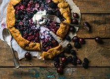 Garden berry crostata sweet pie with melted vanilla ice-cream scoop Stock Image