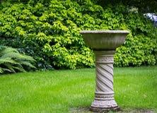 Garden bird concrete stone fountain. Green grass background stock photography