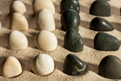 Garden of black and white stones, sticking out of the sand in th Stock Photography